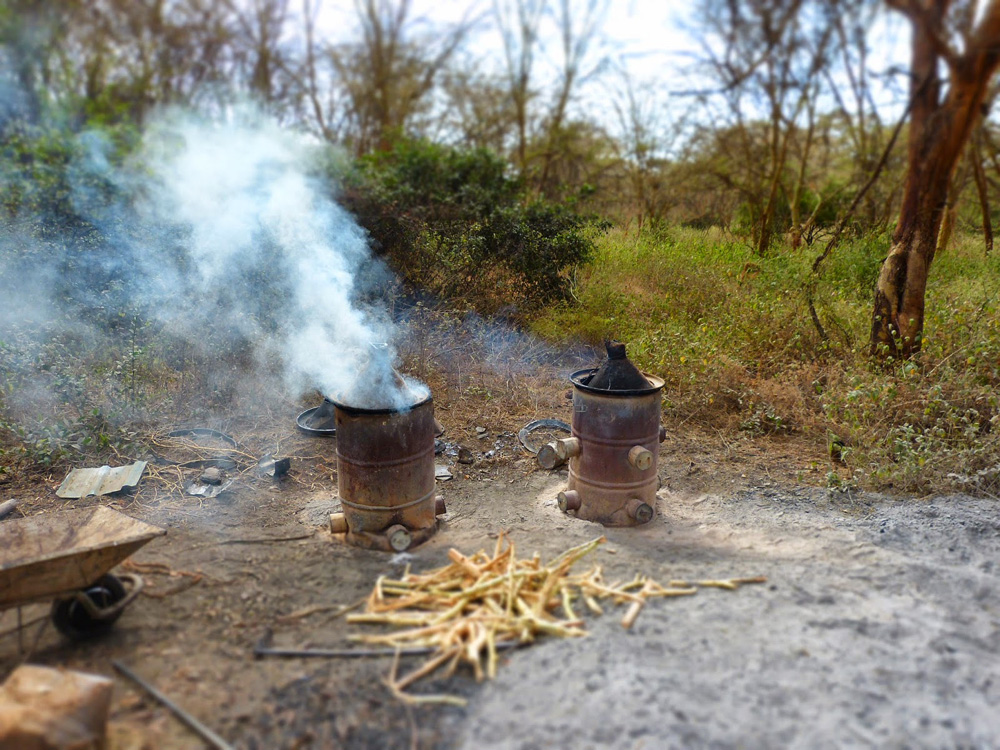A pair of  large charcoal kilns carbonizing sun-dried branches into charcoal. Photo courtesy of Cookswell Energy Saving Jikos. http://www.kenyacharcoal.blogspot.com/