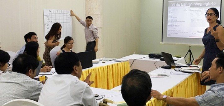 Elisabeth Simelton (standing, right), ICRAF researcher working with CCAFS, and workshop participants discussing a sample agricultural advisory. Photo: World Agroforestry Centre/Le Van Hai