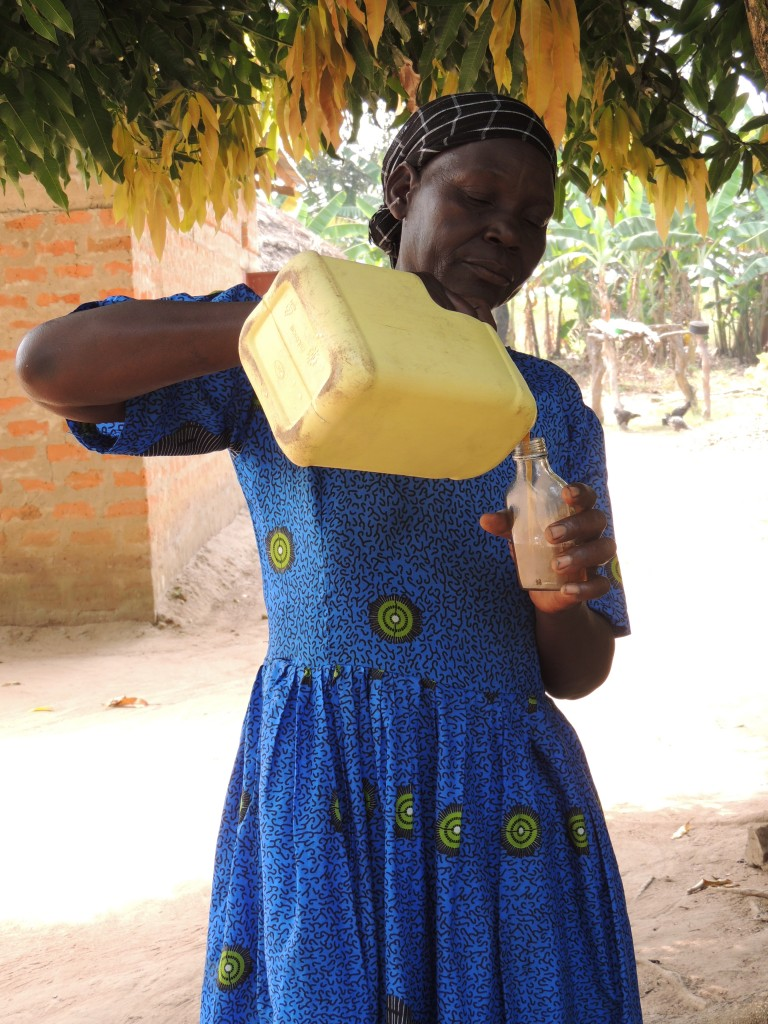 In Abia, Northern Uganda, farmer and grandmother Catherine Ekuka, 63, decants shea oil for cooking. Photo CWatson/ICRAF