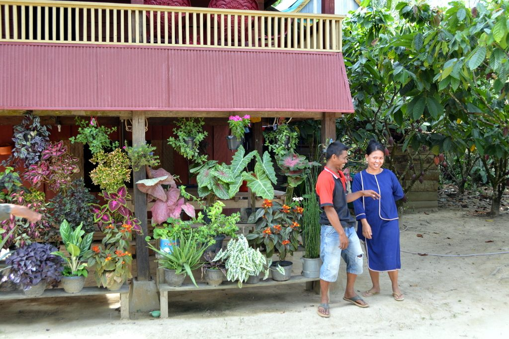 Mr Agustang and Ms Ramlah in front of their colourful house and cacao-pepper farm