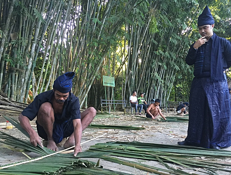Saputra watching a fellow Kajang at work weaving a palm-leaf roof panel. Photo: World Agroforestry Centre/Amy Lumban Gaol