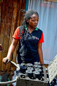 Youth group member from Kahawa-Soweto in Nairobi making briquettes in a metal press. Photo by Sherry Odeyo/ICRAF